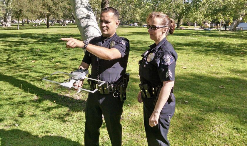 Officers show off a mobile receiver used in tracking down people who are enrolled in Project Lifesaver.