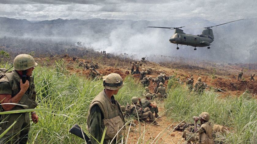 Helicopter lands while troops wait in foreground and grass fire burns in background in June 1968. (A