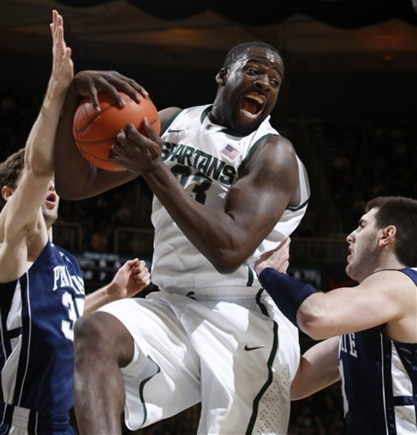 Michigan State's Draymond Green, center, pulls down a rebound between Penn State's Billy Oliver, left, and Sasa Borovnjak during the first half of an NCAA college basketball game on Wednesday, Feb. 8, 2012, in East Lansing, Mich. (AP Photo/Al Goldis)