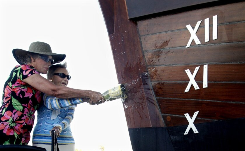 Carolyn Sharp (L) and Vi McKinney smash a bottle of bubbly against the bow of the San Salvador during its christening ceremony Wednesday afternoon. The galleon replica was built over the past four and a half years by Maritime Museum of San Diego workers and volunteers.