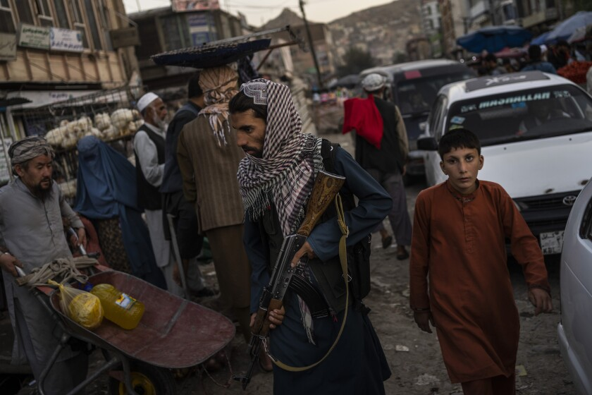 Taliban fighters patrol a market in Kabul's Old City