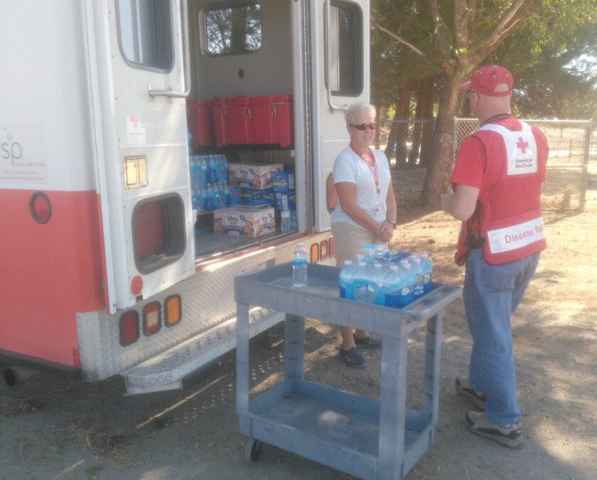 Red Cross volunteers, Laurie Katz and Royce Wolfe, offer water and snacks at Ramona Old Rodeo Grounds in a past fire season.