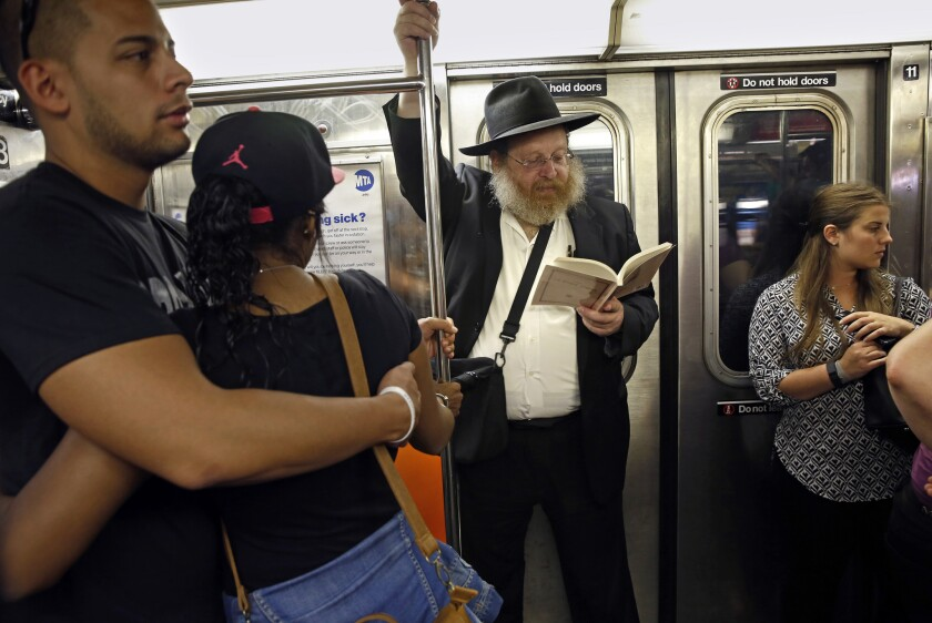 Rabbi Yosef Katzman, center, and others on the New York subway in September 2014.