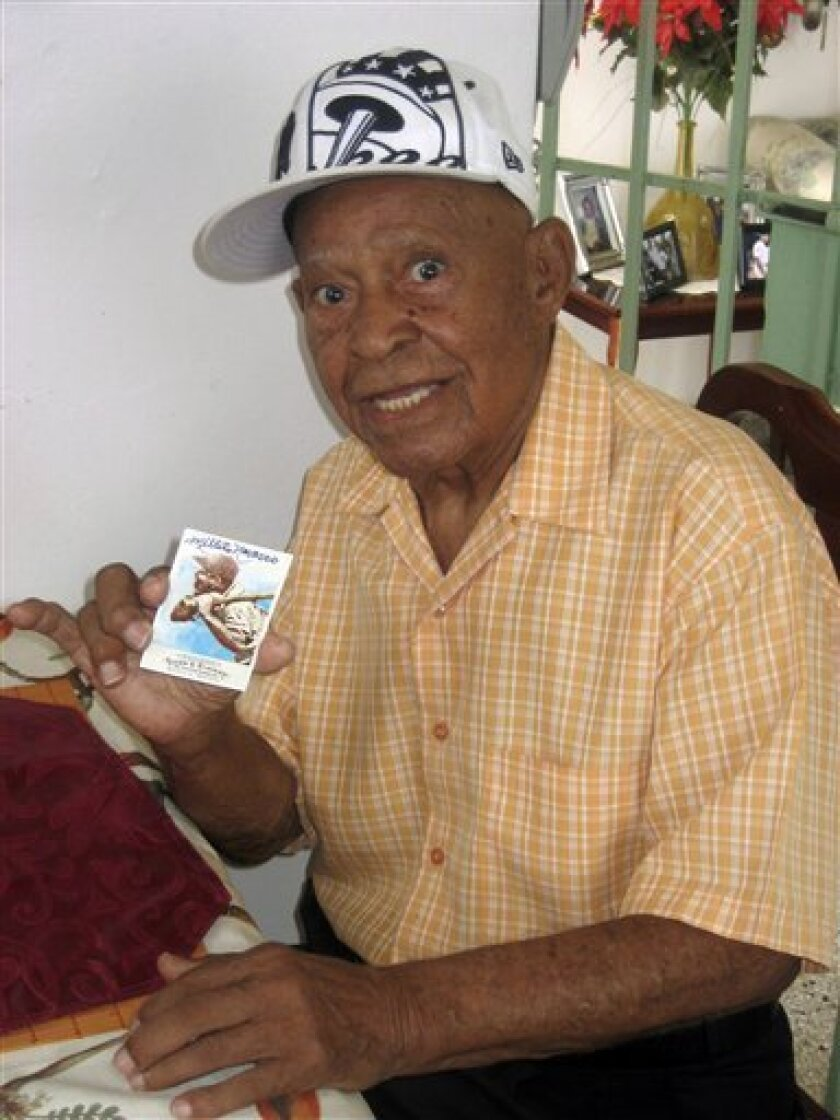 "FILE - In this July 29, 2010 file photo, former professional baseball player Emilio ""Millito"" Navarro, 104, holds his signed baseball card while posing for a picture in his home in Ponce, Puerto Rico. Navarro, who was believed to be the last surviving player of the Negro American League, died Saturday, April 30, 2011, in his Caribbean homeland of Puerto Rico. He was 105. (AP Photo/Danica Coto, file)"