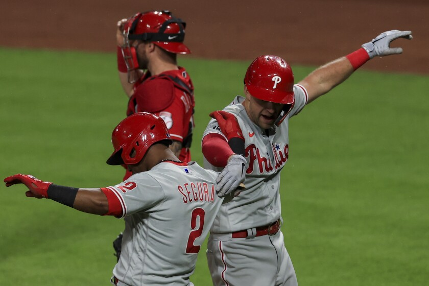 Philadelphia Phillies' Jean Segura, left, celebrates the two-run home run by Rhys Hoskins, right, during the sixth inning of a baseball game against the Cincinnati Reds in Cincinnati, Tuesday, June 1, 2021. (AP Photo/Aaron Doster)
