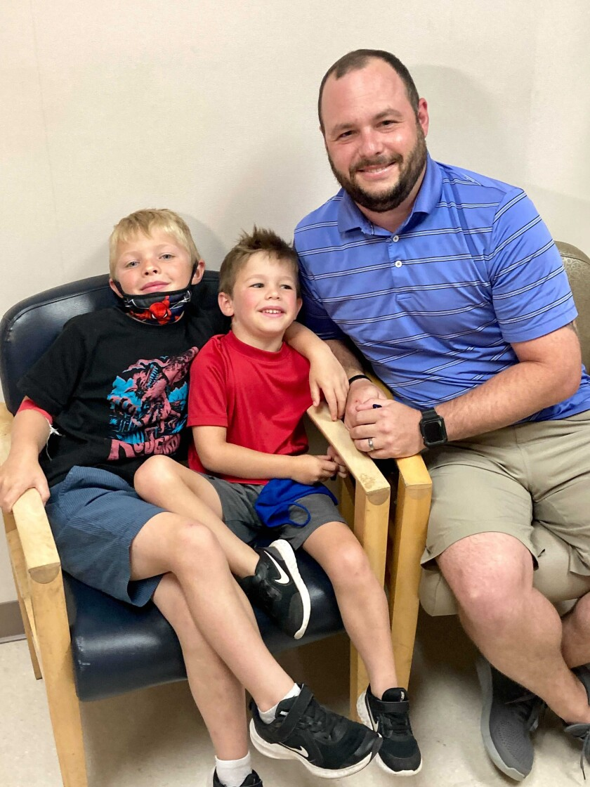 From left, 7-year-old Russell Bright, 5-year-old Tucker Bright, and dad Adam Bright pose for a picture at Ochsner Medical Center in Jefferson, La., Monday, June 7, 2021. Tests of Pfizer's COVID-19 vaccine started Monday in Louisiana for children ages 5 through 11. (AP Photo/Stacey Plaisance)