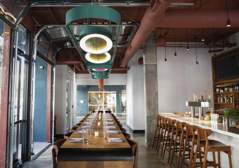A cherry wood long communal table is located near the bar inside of Socalo, the new restaurant from Susan Feniger and Mary Sue Milliken in Santa Monica.