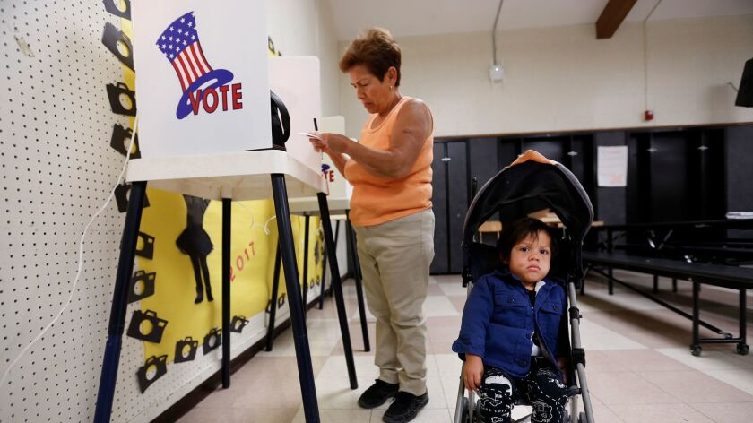 LOS ANGELES, CA - JUNE 6, 2017 -- Theresa Sandoval checks her ballot while caring for her 1 year old