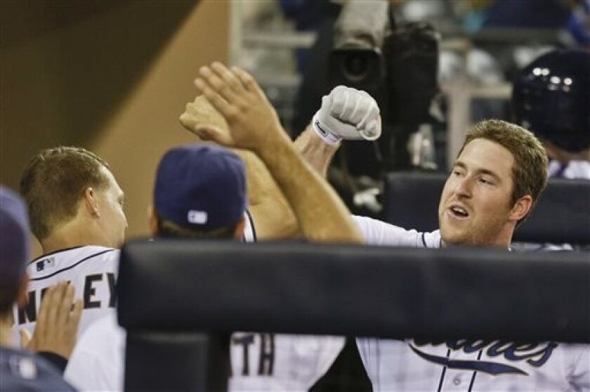 One of eight Padres to make their major league debuts in 2013, second baseman Jedd Gyorko, right, bangs forearms with Nick Hundley after hitting a run in what's become a remarkable rookie season. (AP Photo/Lenny Ignelzi)
