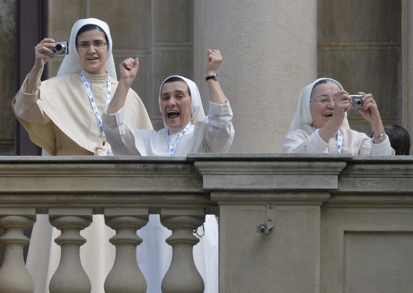 Nuns cheer and take pictures from a balcony as Pope Francis arrives to give the Angelus prayer at Sao Joaquim Palace in Rio de Janeiro.