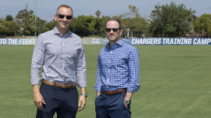 A.G. Spanos, left, Chargers president of business operations, and his brother John Spanos, president of football operations, stand on the team's new training camp field at the Jack R. Hammett Sports Complex in Costa Mesa.