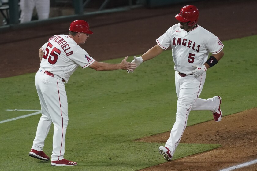 The Angels' Albert Pujols is greeted by third base coach Brian Butterfield.