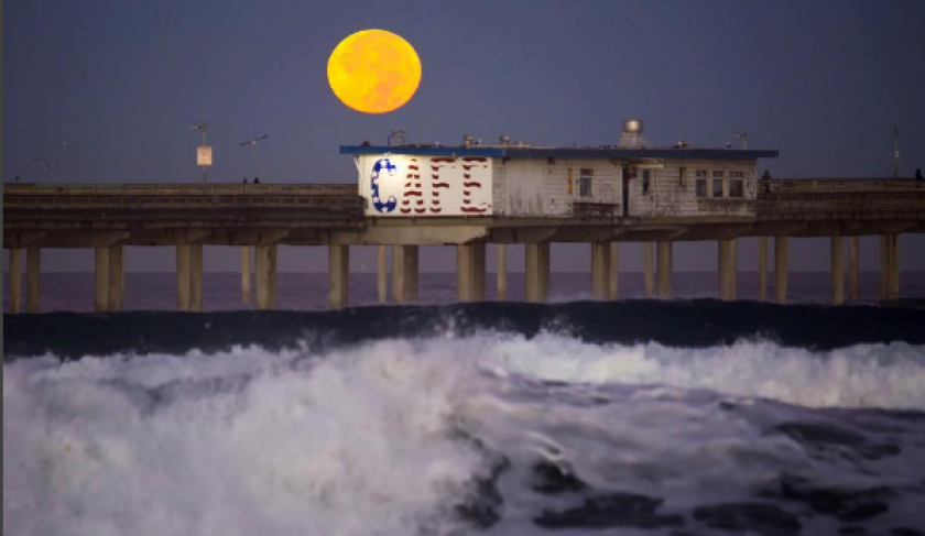 The supermoon hovering above the pier at Ocean Beach (Howard Lipin - SDUT)