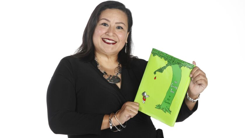 """Star Rivera-Lacey, vice president of student services for San Diego Continuing Education in the San Diego Community College District, holds a copy of """"The Growing Tree"""" by Shel Silverstein """"because I believe in being motivated by love and giving back..."""""""