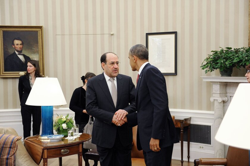 Iraqi Prime Minister Nouri Al-Maliki, left, shakes hands with U.S. President Barack Obama in the Oval Office at the White House in Washington, D.C.