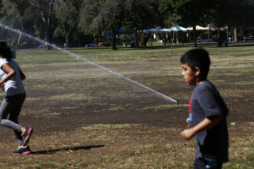 Two children run past sprinklers at Warner Ranch Park in the San Fernando Valley in June. New reports show Angelenos cut water use by 21% in July.