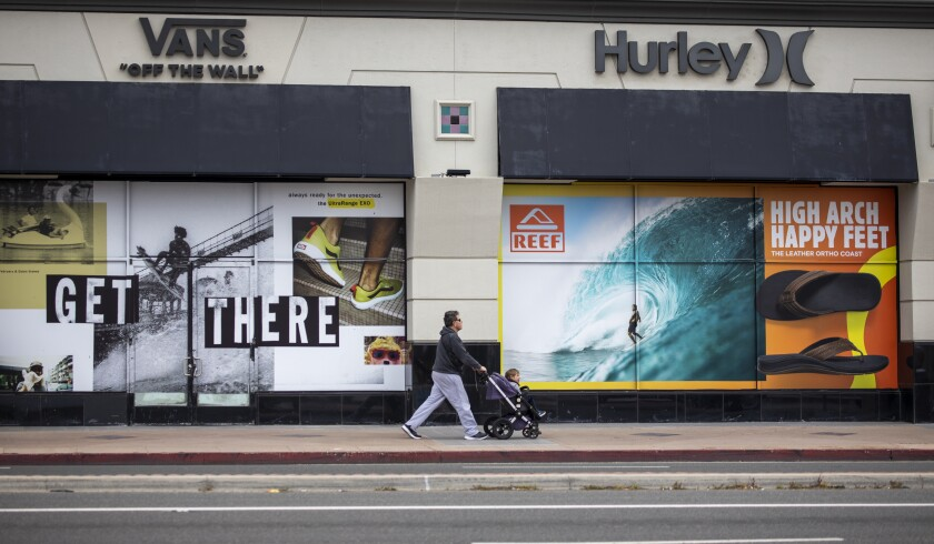 A man takes his child on a walk in downtown Huntington Beach amid coronavirus restrictions last week.