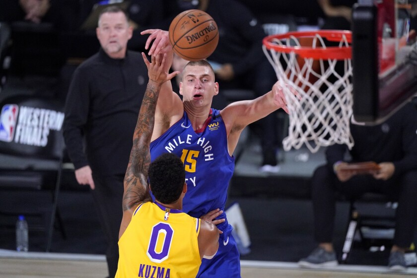 Nuggets center Nikola Jokic lofts a pass over Lakers forward Kyle Kuzma during Game 1.