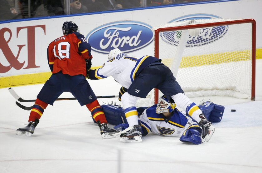 St. Louis Blues goalie Brian Elliott, bottom, and defenseman Jay Bouwmeester, top, make a save against Florida Panthers right wing Reilly Smith (18) during the third period of an NHL hockey game, Friday, Feb. 12, 2016, in Sunrise, Fla. The Blues defeated the Panthers 5-3. (AP Photo/Wilfredo Lee)