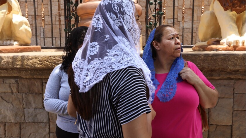 EAST LOS ANGELES, CA - JUNE 5, 2019 - - Congregants stand in front of La Luz Del Mundo Church as oth
