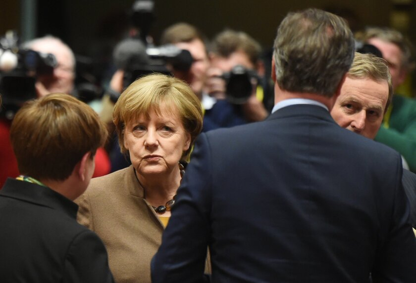 British Prime Minister David Cameron speaks to Irish Prime Minister Enda Kenny, right, as and German Chancellor Angela Merkel, second left, looks on during a round table meeting at an EU summit in Brussels on Thursday, Feb. 18, 2016. European Union leaders are holding a summit in Brussels on Thursd