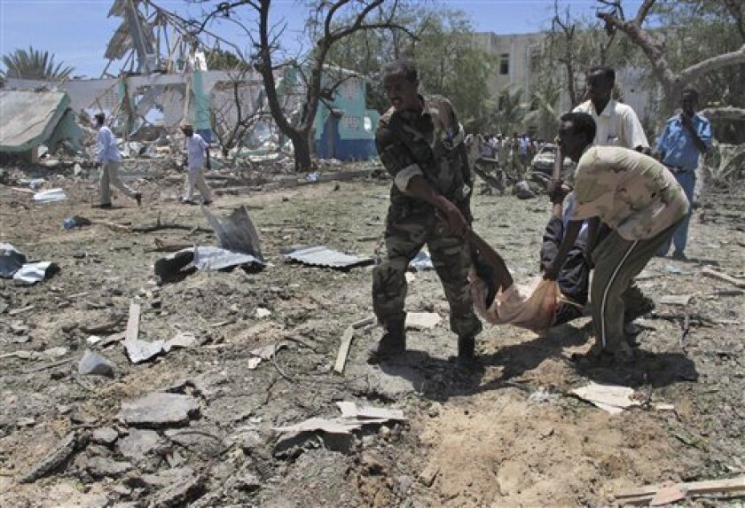 Somalis carry a wounded man at the scene of an explosion in Mogadishu, Somalia, Tuesday, Oct. 4, 2011. A rescue official says at least 55 people were killed after a car laden with explosives blew up in front of the Ministry of Education in the Somali capital of Mogadishu. The al-Qaida-linked militant group al-Shabab immediately claimed responsibility for the attack on a website it uses, after more than a month of relative calm in Mogadishu.(AP Photo/Mohamed Sheikh Nor)