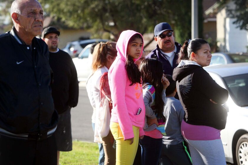Neighbors look on Tuesday, Dec. 31, 2013, as Fontana, Calif. police investigate the house where a family of four were found shot to death on Monday night. (AP Photo/The Press-Enterprise, Kurt Miller)