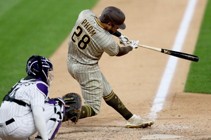 Padres outfielder Tommy Pham hits a three-run homer in the ninth inning against the Rockies on Friday.