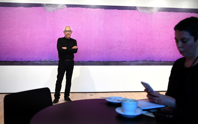 """Anthony Hernandez stands before his mural-sized print """"South Central,"""" 2015, at SFMOMA."""