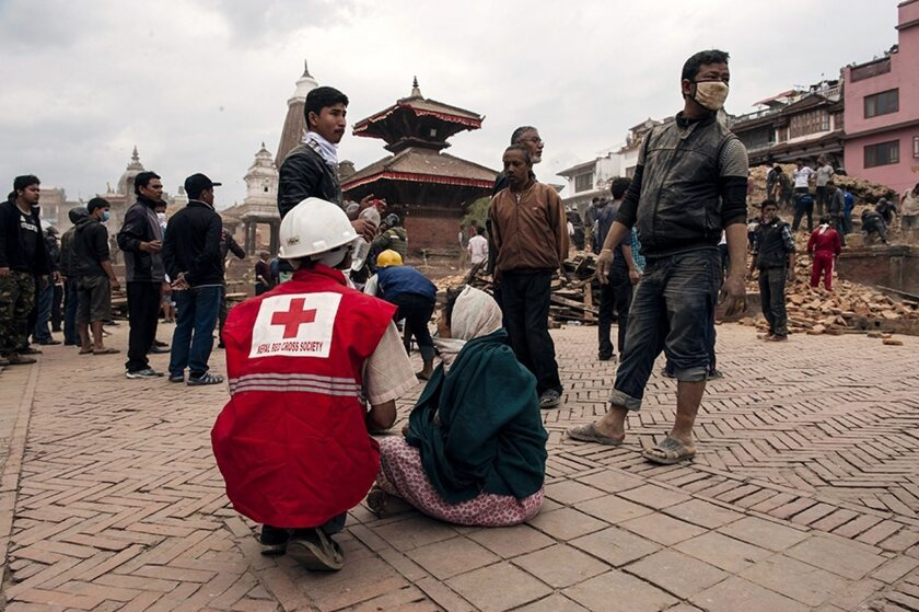 A photo provided by the International Federation of the Red Cross shows a rescue worker from the Nepal Red Cross Society helping injured people in Kathmandu, Nepal, on April 25, 2015.