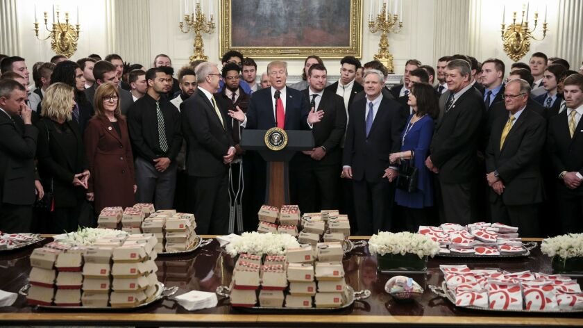 President Trump speaks behind a table full of fast food as he welcomes the North Dakota State Bison to the White House on March 4.