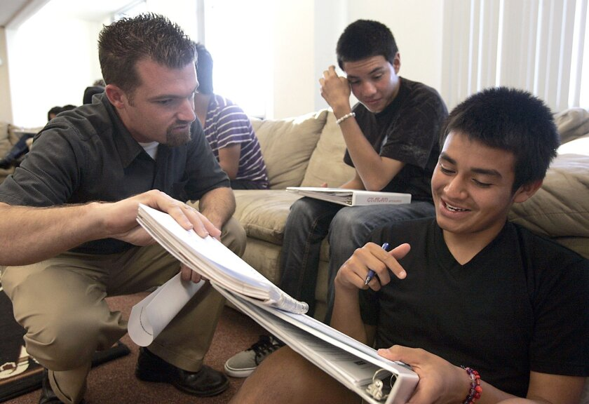 Chris Yanov (left), executive director of Reality Changers, advises Allen Mauricio on his essay while Gustavo Hernandez (center) watches. Yanov started the successful college prep program that helps students get into college.