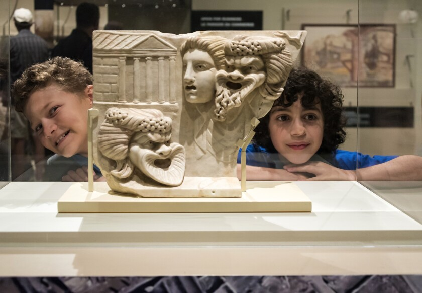 Two boys at the Royal Ontario Museum standing beside a marble slab sculpture depicting faces of a young woman and two old men with open mouth.