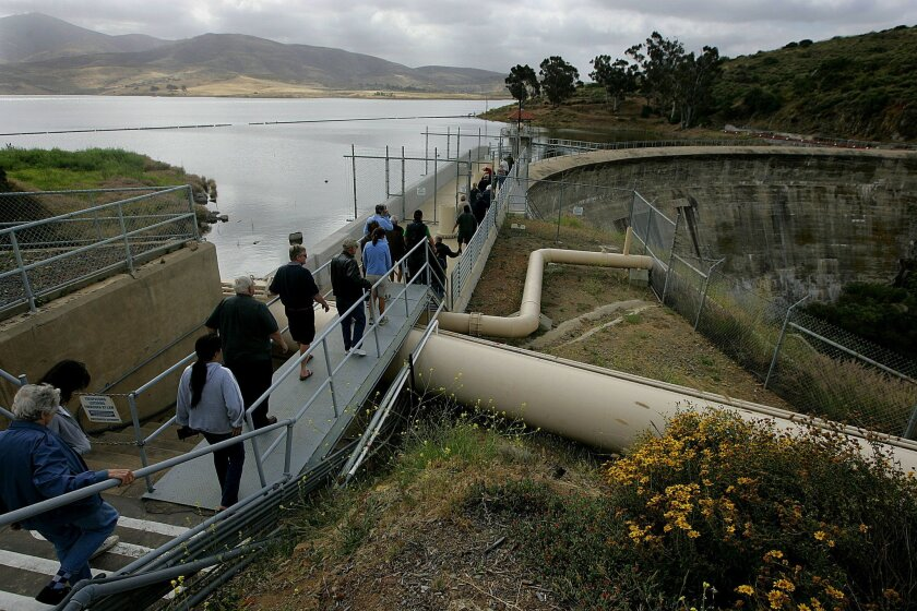 Visitors enjoy a rare, up-close look at Sweetwater Reservoir Dam last week during a tour of the Sweetwater Reservoir. Below, Kayalan McIntyre (left), 10, and Crystal Relvea look down at a large fish along with other visitors during the tour.