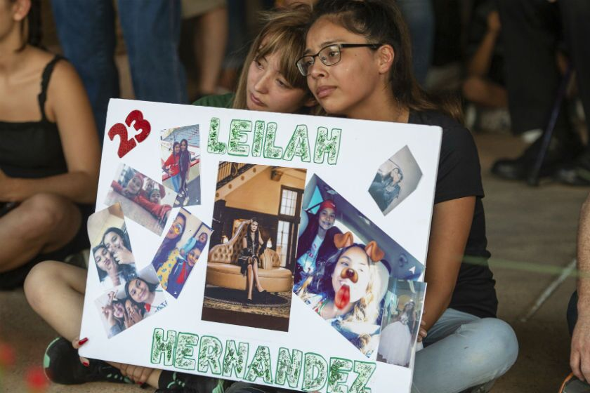Two girls hold a sign in memory of a victim of the West Texas mass shooting