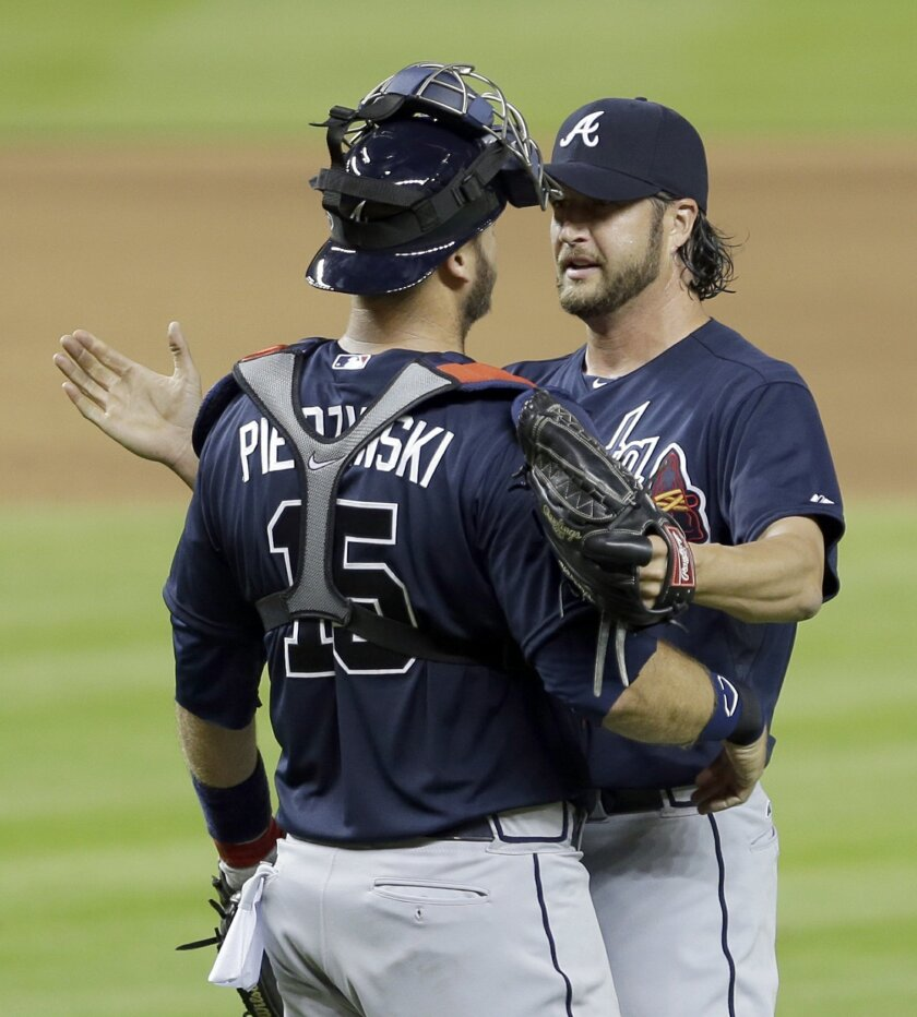 Atlanta Braves relief pitcher Jason Grilli, right, is congratulated by A.J. Pierzynski (15) after a 2-0 win against the Miami Marlins at the end  of a baseball game, Wednesday, April 8, 2015, in Miami. (AP Photo/Alan Diaz)