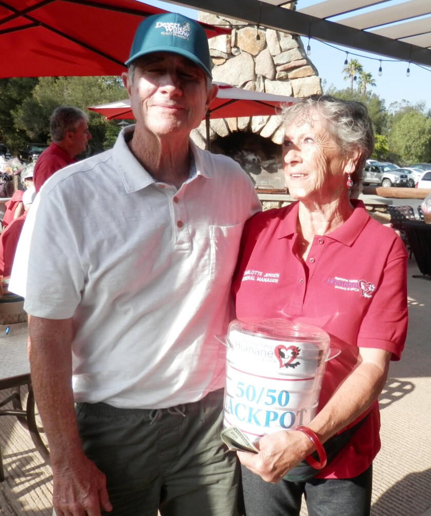 One of the Golfing for a Cause participants celebrates with Humane Society General Manager Charlotte Jensen.