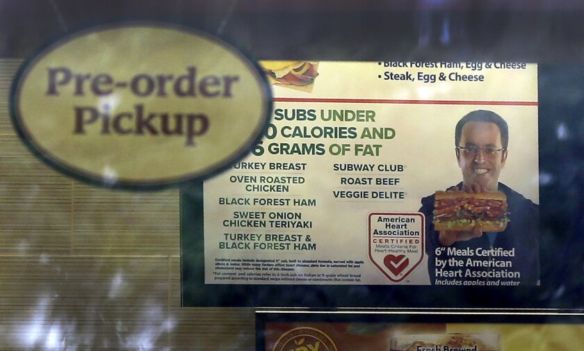 A photo of Subway restaurant spokesman Jared Fogle is seen on a menu board hanging inside one of its locations Tuesday, July 7, 2015, in St. Louis. FBI agents and Indiana State Police raided the home of Fogle on Tuesday, removing electronics from the property and searching the house with a police d