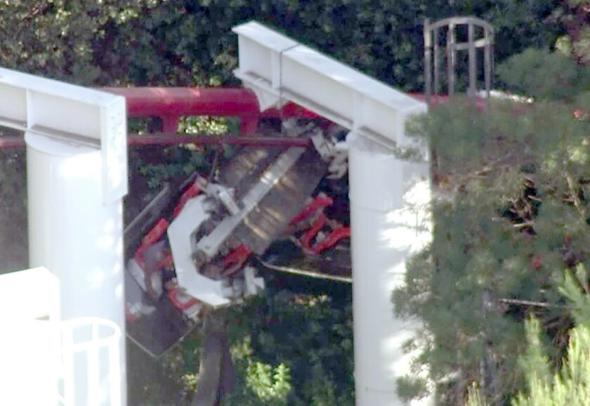 About two dozen people were trapped on the Ninja roller coaster at Magic Mountain when the front car derailed. Four people suffered minor injuries, authorities said.