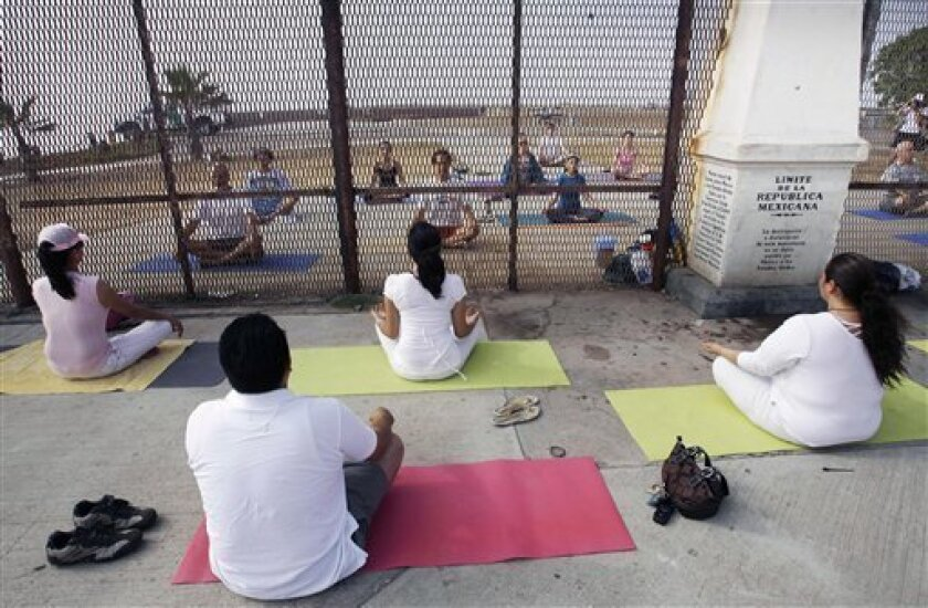 """In this Sunday, June 22, 2008 photo, residents practice yoga on both sides of the U.S.-Mexico border fence as they take part in  the """"Yoga without borders"""" encounter in Tijuana, Mexico. The top U.S. Border Patrol official in San Diego said Friday Jan. 9, 2009 that he closed this half-acre oceanfr"""