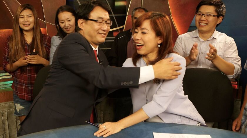 Harry Chang hugs his co-anchor Christine Chiang after their final broadcast Friday.
