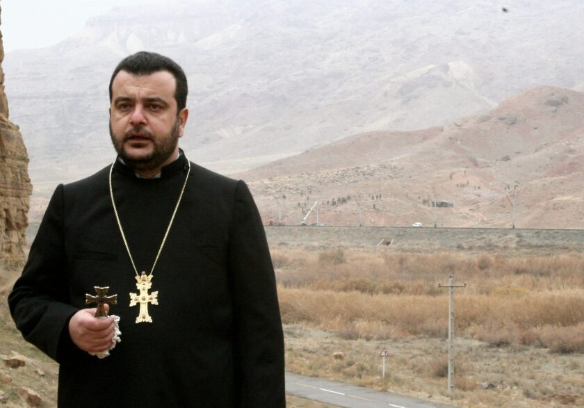 Bishop Nshan Topouzian, photographed in 2005 praying as soldiers across the border destroyed khachkars.