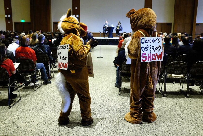 Two people dressed as a dog and a pony stood at the back of a Wednesday afternoon forum with CSU Chancellor Timothy White at San Diego State University. The faculty union is asking for a 5 percent raise and is threatening a strike.