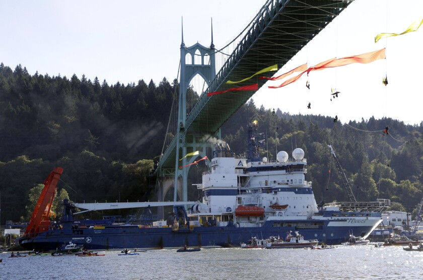 The Shell icebreaker MSV Fennica heads up the Willamette River in Portland, Ore., last month under Greenpeace activists hanging from a bridge.