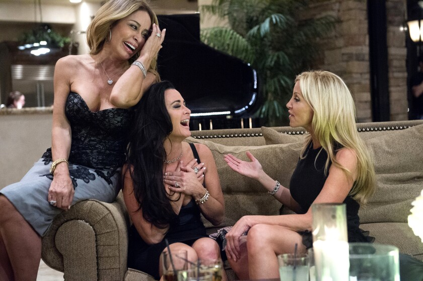 Three women dressed in black laughing on a sofa