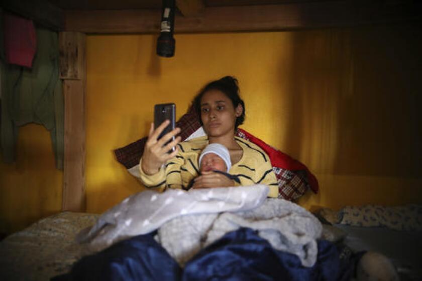 En esta imagen del 12 de junio de 2019, la adolescente migrante Milagro de Jesús Henríquez Ayala, de El Salvador, en la cama con su hijo recién nacido, Alexander, mientras ve Bob Esponja en su celular, en el refugio de la iglesia Ágape Misión Mundial, en Tijuana, México. (AP Foto/Emilio Espejel)