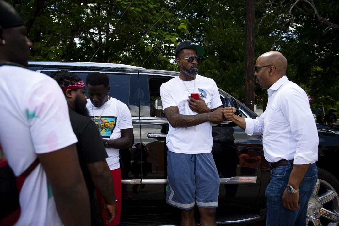 Stephen Jackson, center, greets civil rights attorney Daryl Washington in Houston's Third Ward.