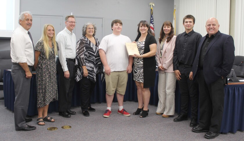 Ramona Unified School District trustees, Superintendent Theresa Grace and student school board members surround Montecito High School senior Nathan Burchard as board President Dawn Perfect presents him with his Inspirational Student of the Month plaque.