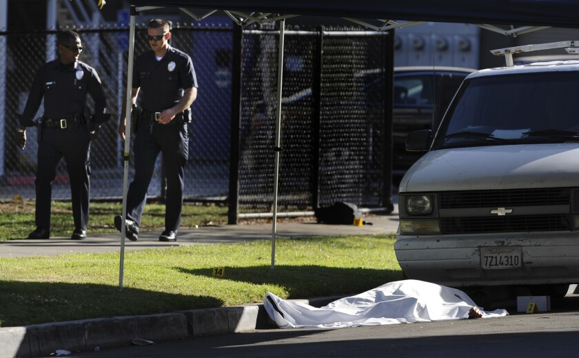 LAPD officers walk by a body in front of Woodbine Park in the Palms area of Los Angeles. Two shootings left one person dead and at least three others wounded.