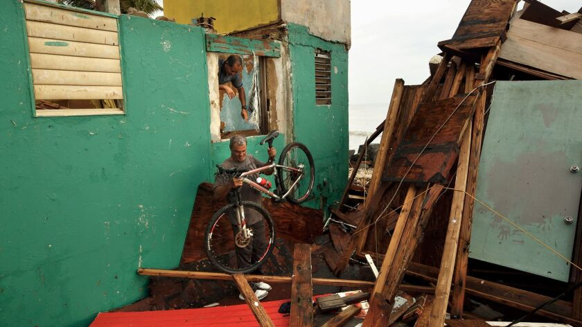 """Ivan Lopez, 51, helps a neighbor with his badly damaged home. """"Here I was born and here I will die,"""" Lopez said."""
